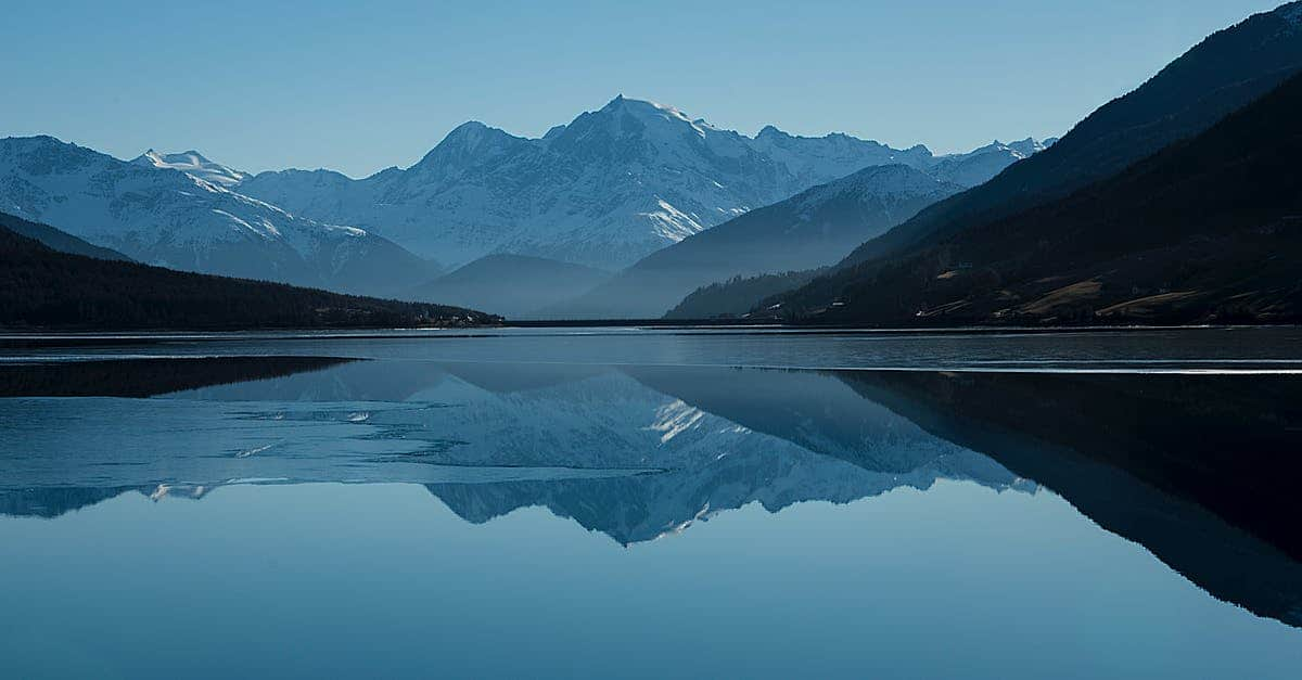 A body of water with a mountain in the background