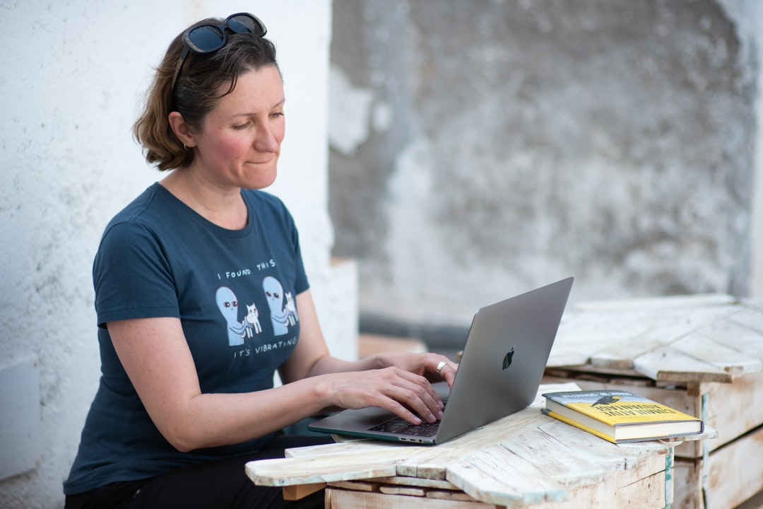 A woman using a laptop computer sitting on top of a building